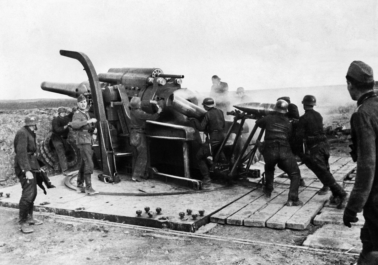 Truppe tedesche caricano l'artiglieria pesante. Simili armamenti venivano utilizzati anche per difendere la città e il fronte orientale