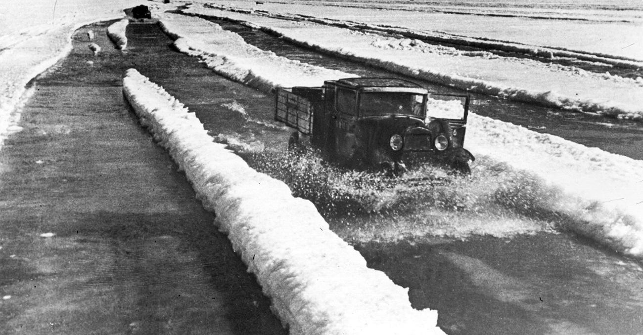 """Lungo la """"Strada della Vita"""", l'unica via che collegava Leningrado al mondo esterno, attraverso il Lago Ladoga, i mezzi che trasportavano gli approvvigionamenti transitavano giorno e notte. D'estate il lago era attraversato da navi che trasportavano generi alimentari e d'inverno la superficie di ghiaccio era percorsa da camion in cui lo sportello del conducente era stato divelto perché in questo modo se il veicolo fosse finito sotto la crosta di ghiaccio e avesse cominciato ad affondare, il conducente avrebbe avuto la possibilità di balzar fuori"""