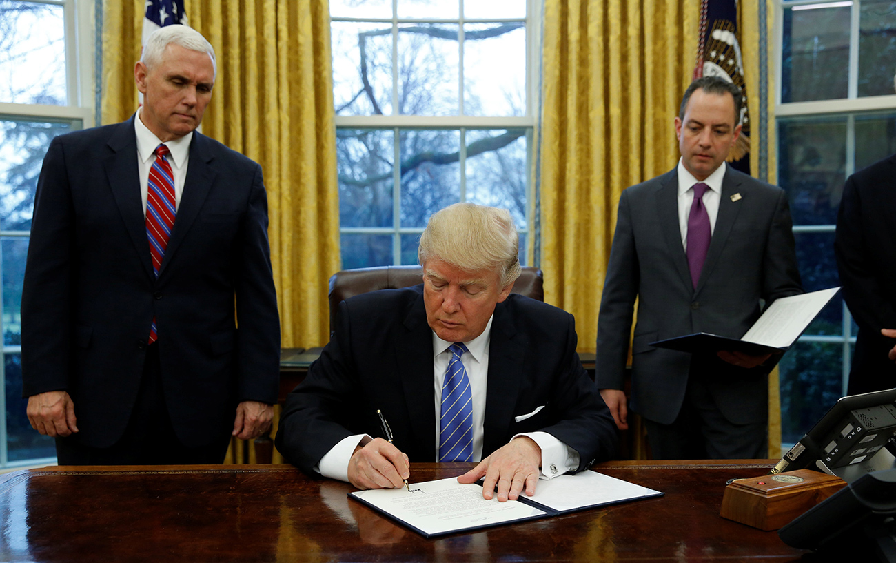 U.S. President Donald Trump signs an executive order on U.S. withdrawal from the Trans-Pacific Partnership while flanked by Vice President Mike Pence (L) and White House Chief of Staff Reince Priebus (R) in the Oval Office on Jan. 23, 2017.