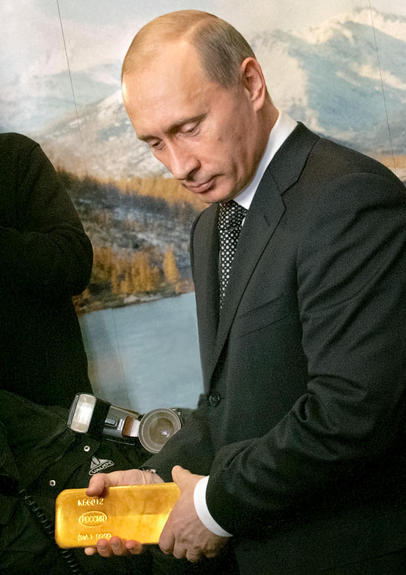 2005年、マガダンで、プーチン大統領が政府金会議の議長を務めた際、金のインゴットを手に取る=AP通信