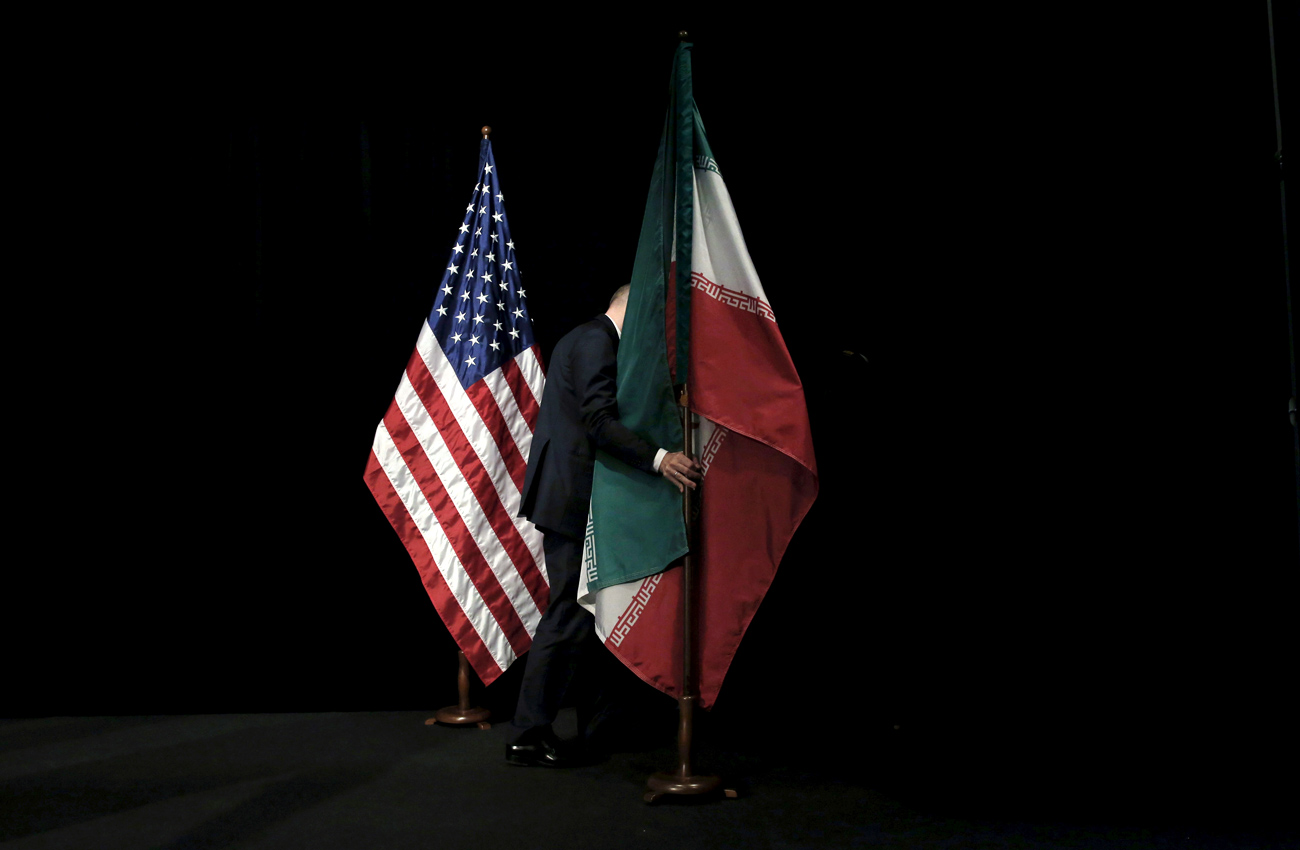 Experts say that Russia may not join U.S. efforts to contain Iran, despite the formal improvement of Russian-U.S. relations. Photo:  A staff member removes the Iranian flag from the stage after a group picture with foreign representatives during the Iran nuclear talks at the Vienna International Center.