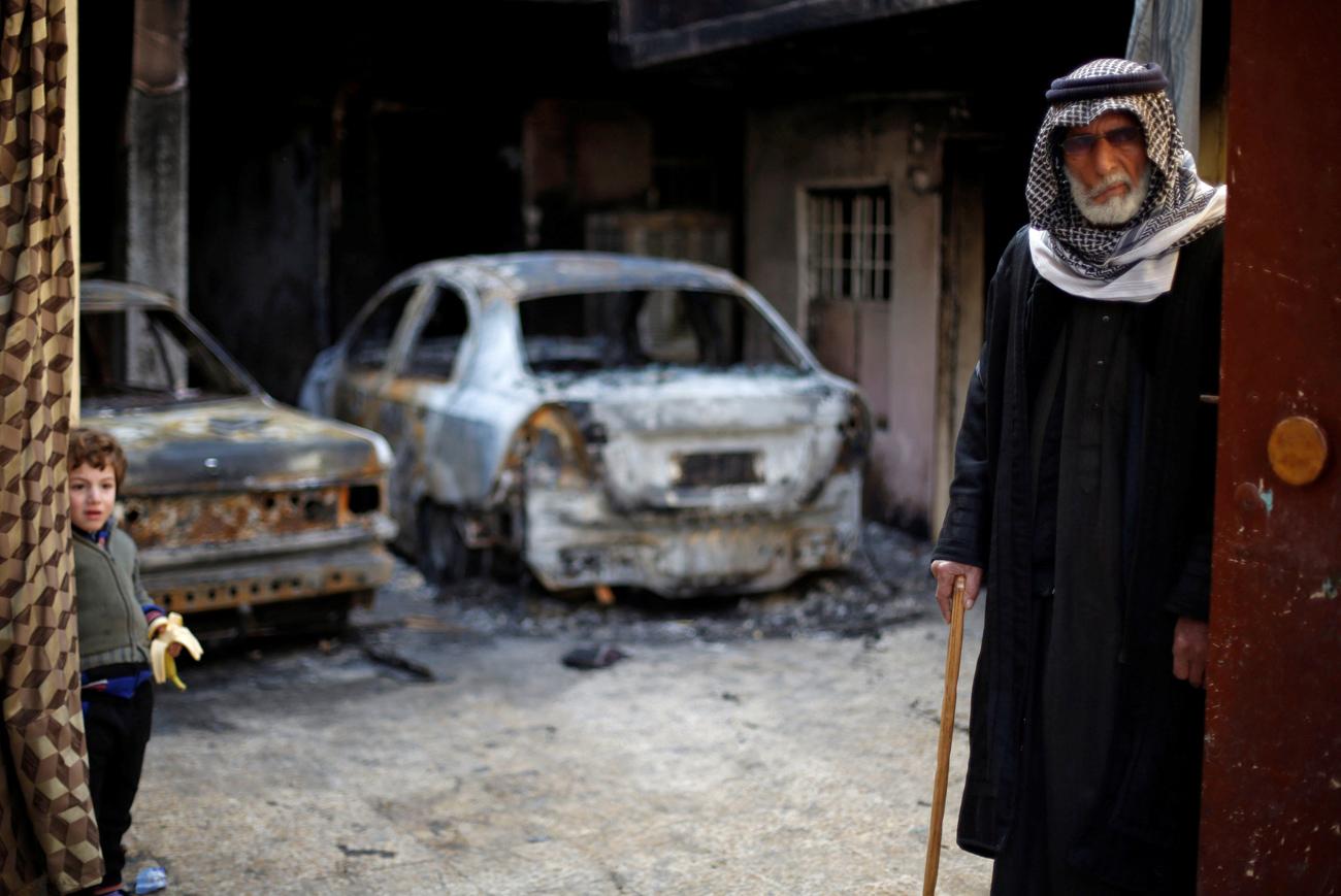 Homem e criança em frente a casa incendiada por EI fotografados minutos antes de deixar Mossul