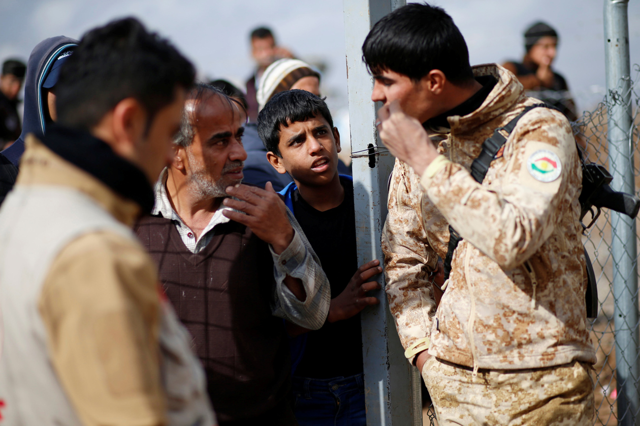 Para pengungsi Irak yang melarikan diri dari pertempuran di Mosul berbicara dengan Tenntara Peshmerga di kamp Khazer, Irak. Sumber: Reuters