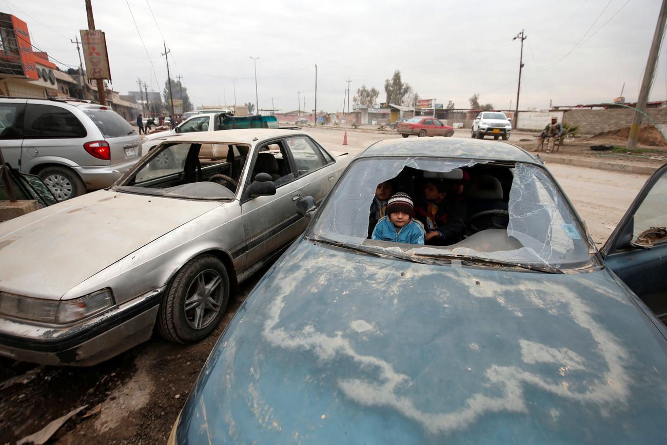 Anak-anak yang menjadi korban perang tampak dari kaca mobil yang pecah di  sebuah jalan di Mosul, Irak.