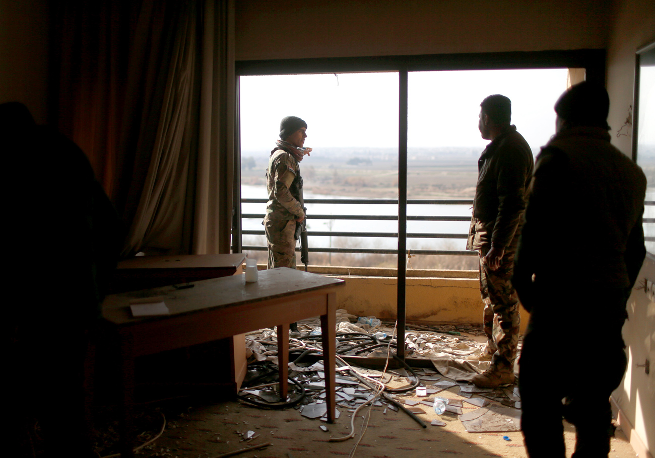Iraqi soldiers look out from a damaged room in the five-star Ninewah Oberoi Hotel in Mosul city, Mosul, Iraq.