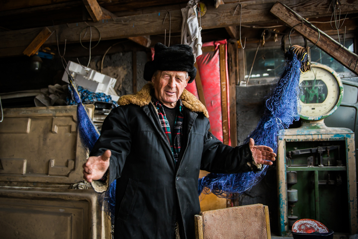 Nikolay Semenovich Konovalov, a fisherman from Khakassia, at his home, shows the size of the Siberian fish he has caught