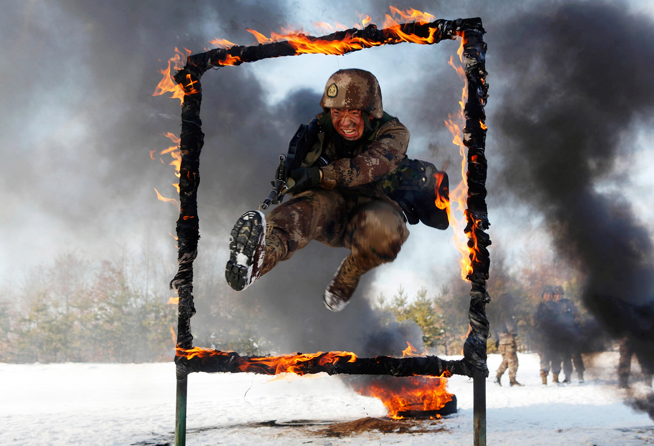 A People's Liberation Army soldier jumps over a burning obstacle during a training session on a snowfield, in Heihe, Heilongjiang province.