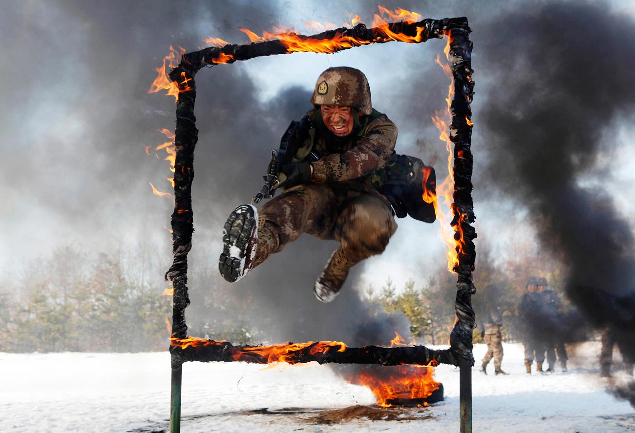 Seorang prajurit Tentara Pembebasan Rakyat melompati rintangan yang terbakar selama sesi latihan di medan bersalju di Heihe, Provinsi Heilongjiang.