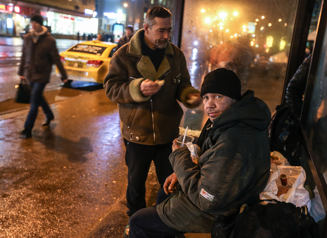 Homeless people seen at a bus stop after receiving food handed out by employees of the Spravedlivaya Pomosch ('Just Aid') Fund.