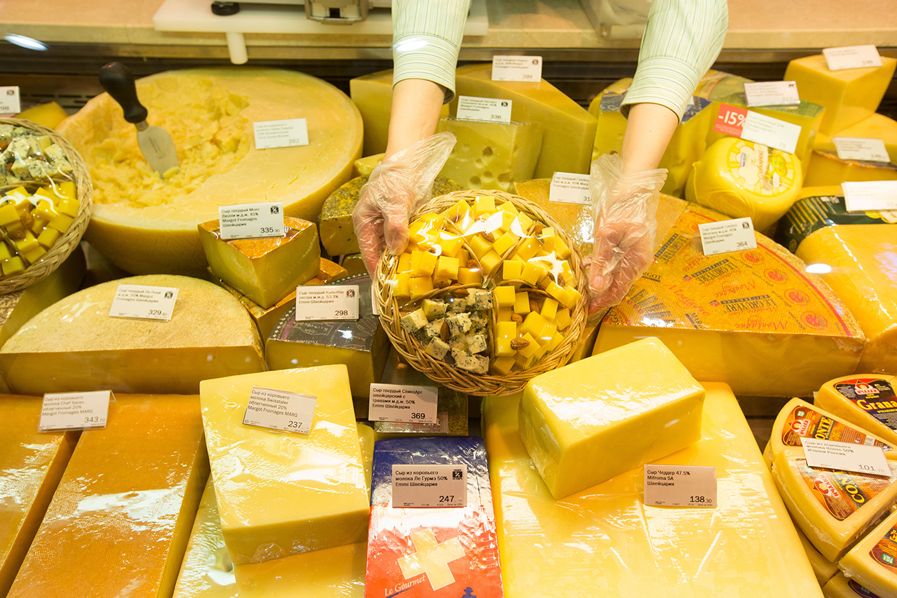 A worker arranges a display of cheeses, including imported products, at the delicatessen counter of an Azbuka Vkusa OOO, which translates as 'Elements of Taste,' supermarket at the Neglinnaya Plaza shopping center in Moscow, Russia.