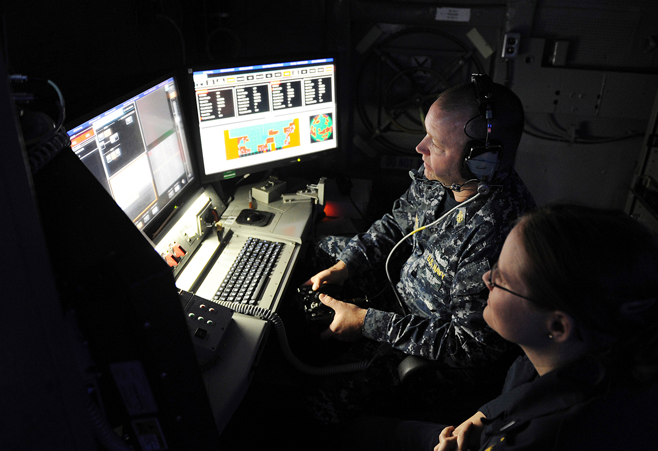 Chief Fire Controlman Brett Richmond (left) and Lt. j.g. Katie Woodard operate the Laser Weapon System (LaWS) installed aboard the USS Ponce during an operational demonstration in the Gulf in Nov. 16, 2014
