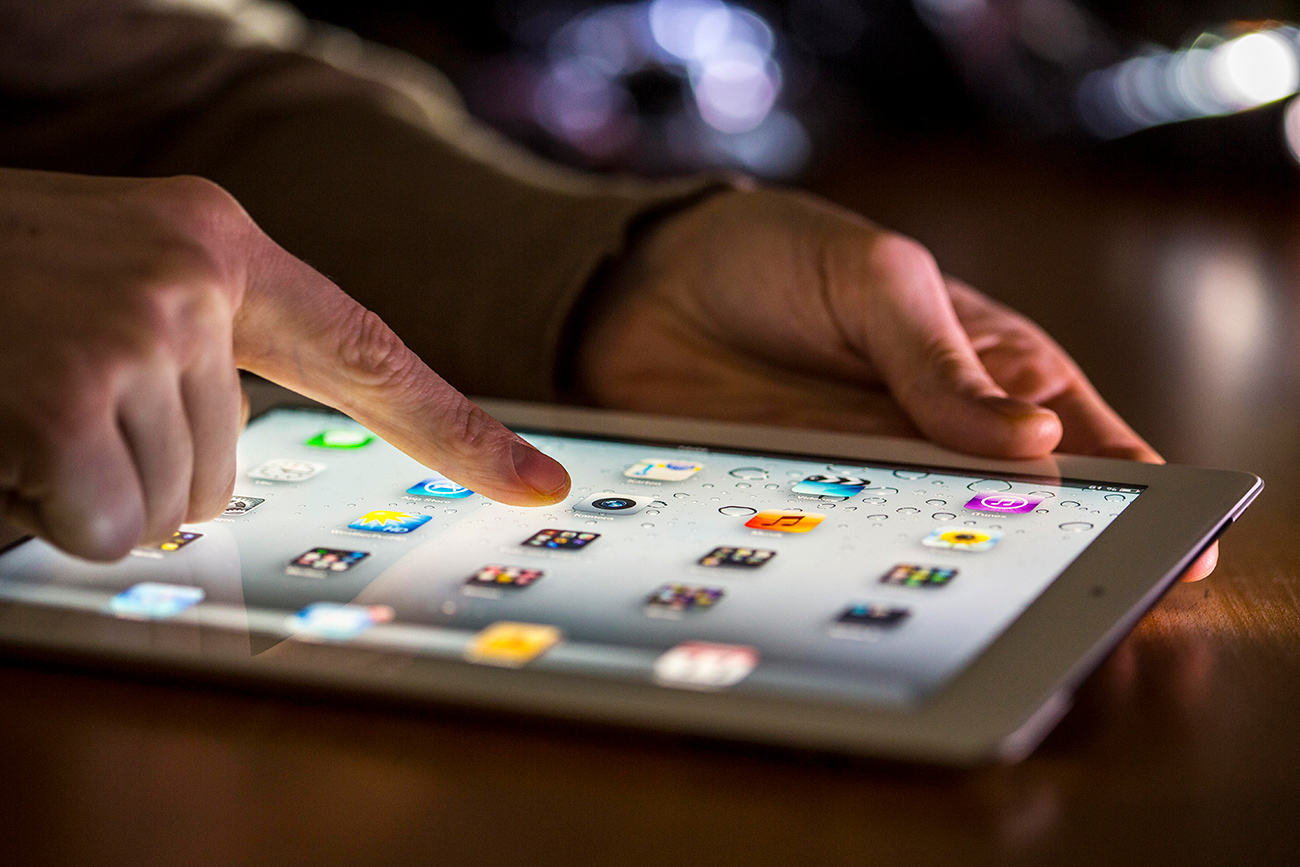Finger touching the touch screen of an Apple iPad