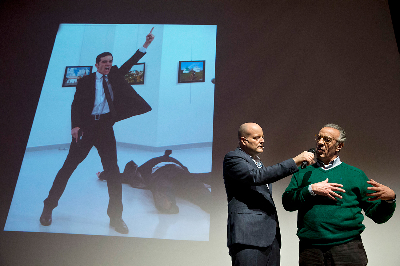 "Il fotografo turco Burhan Ozbilici, a destra, interviene alla cerimonia di premiazione del World Press Photo 2017 ad Amsterdam; sullo sfondo, la sua foto ""Un assassinio in Turchia"", vincitrice del primo premio."
