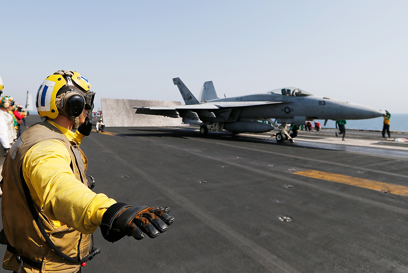 Flight deck crew member confirms the deck is all clear before a F/A-18C Hornet of Strike Fighter Squadron (VFA-87) take offs the aircraft carrier USS George H.W. Bush.