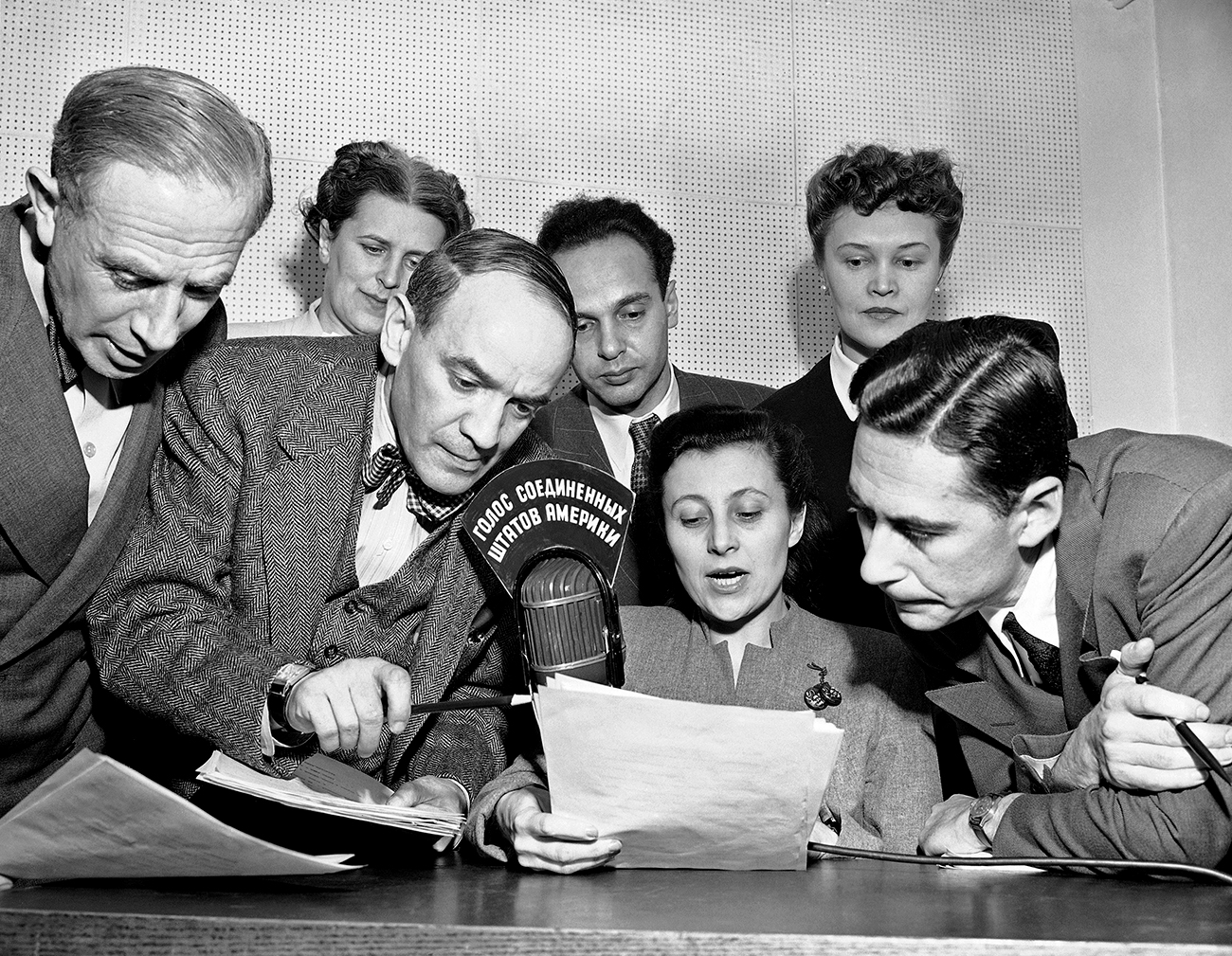 "A group of State Department announcers huddle around the microphone after the initial shortwave broadcast in Russian to Russia from New York City on Feb. 17, 1947. The announcers, Russian-born American citizens, are (front row) Boris Brodenov; James Schigorin; Elena Bates (seated); Victor Franzusoff; (rear row) Katherine Elene; Vladimir Postman and Tatiana Hecker. Sign in Russian on the microphone means ""The Voice of the United States of America."""