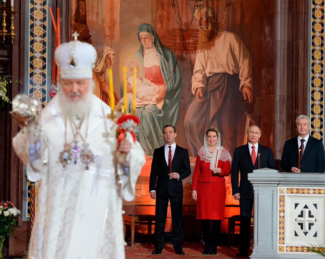 In fondo, da sinistra: il primo ministro russo Dmitrij Medvedv, sua moglie Svetlana Medvedeva, il Presidente russo Vladimir Putin e il sindaco di Mosca Sergej Sobyanin durante una liturgia nella Cattedrale di Cristo Salvatore a Mosca. In primo piano, il Patriarca di Mosca e di tutte le Russie Kirill, 12 aprile 2015\n
