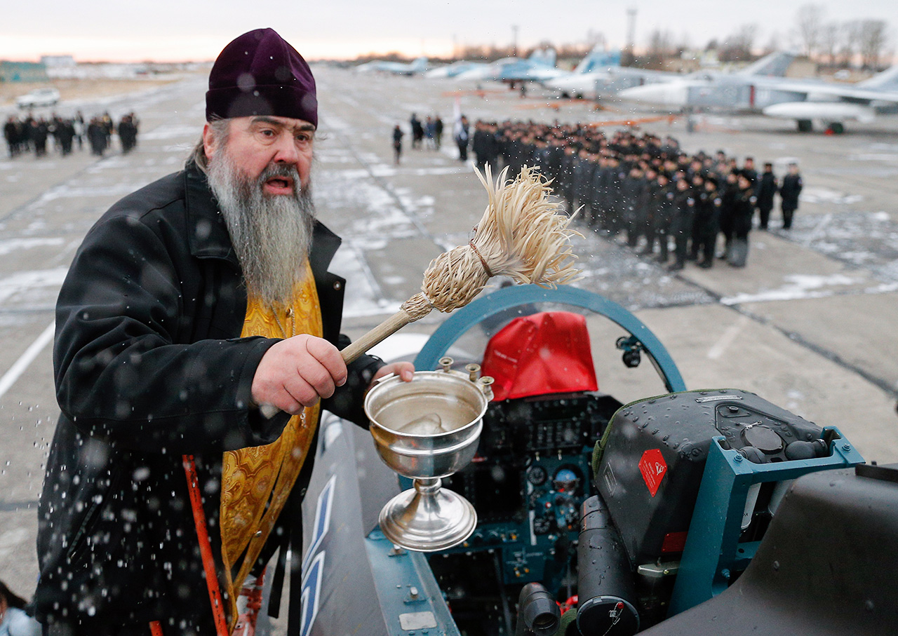 KALININGRAD REGION, RUSSIA - DECEMBER 13, 2016: A priest at a ceremony to welcome the Sukhoi Su-30SM fighter aircraft, the first one to join the Russian Navy Baltic Fleet, at the Chernyakhovsk air base.