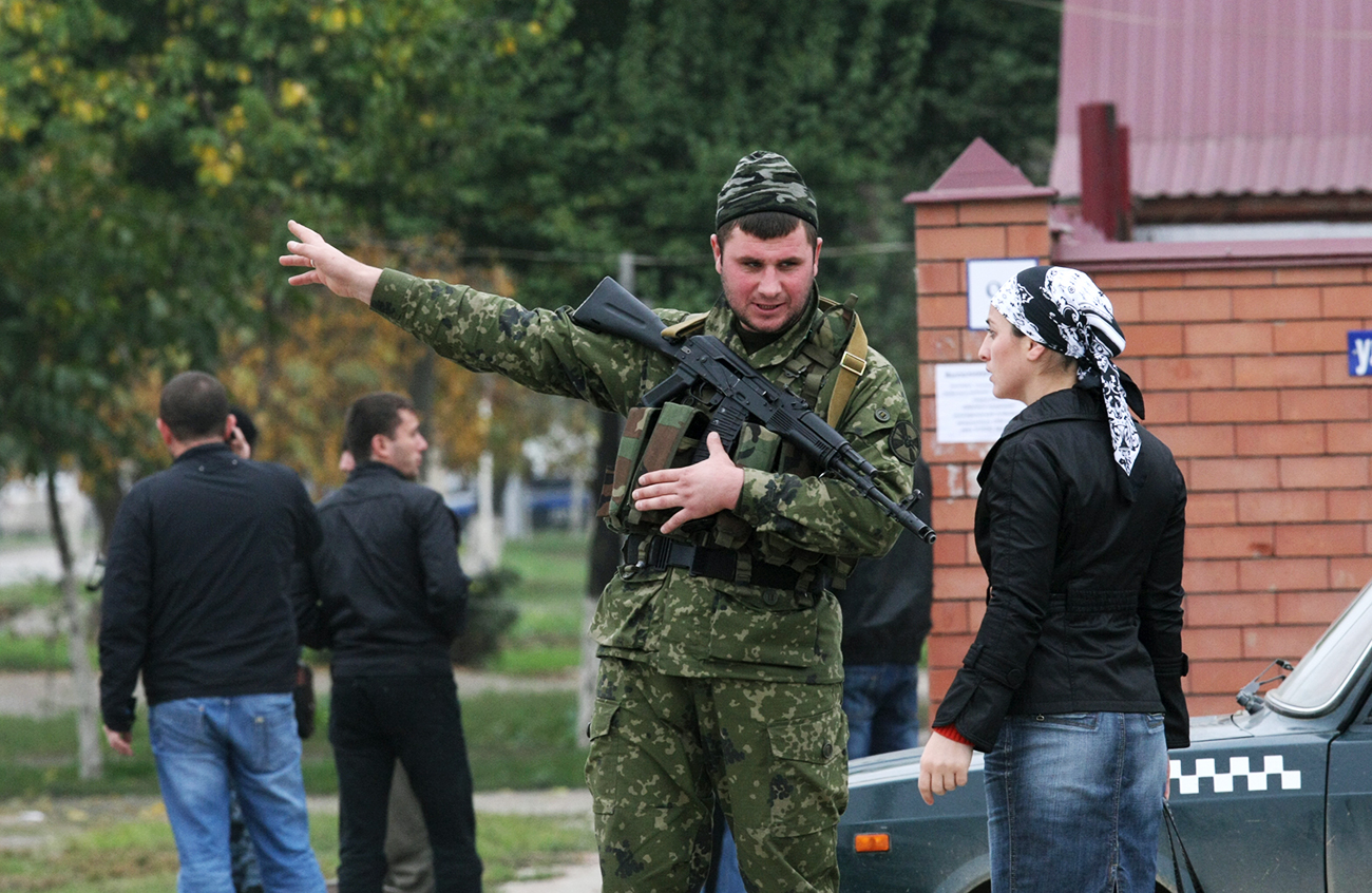 A special security unit officer talks to a woman in Grozny. The security threat remains high in many parts of Chechnya.