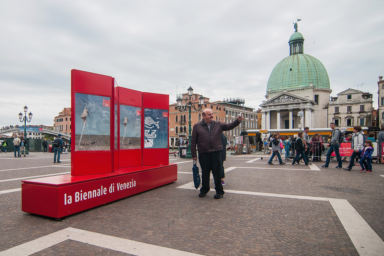 A tourist takes a selfie near a street sign of the Venice Biennale in front of the Santa Lucia railway station.