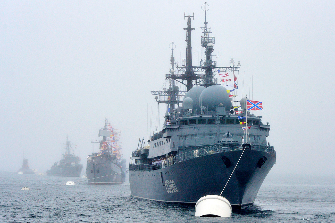 VLADIVOSTOK, RUSSIA. JULY 24, 2015. The Russian Navy SSV 208 Kurily reconnaissance ship (front) during a rehearsal for a Russian Navy Day Parade, in the Amur Bay off Vladivostok.