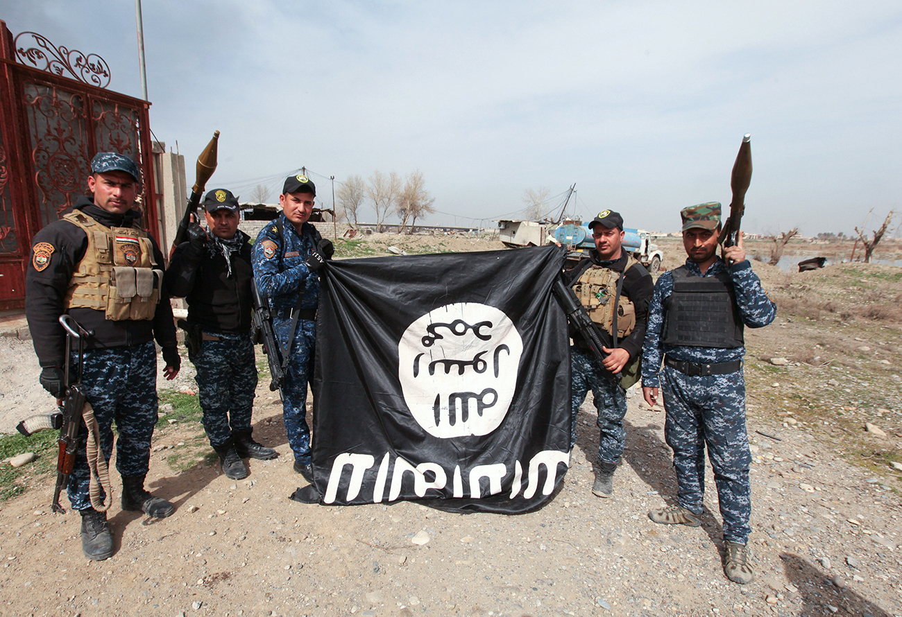 Anggota tentara Irak memegang bendera ISIS yang mereka ambil dalam sebuah pertempuran dengan para teroris itu pada 12 Februari 2017.