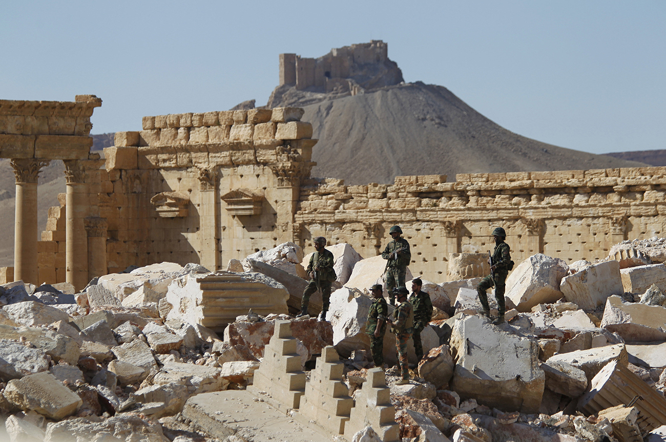 Syrian army soldiers stand on the ruins of the Temple of Bel in the historic city of Palmyra.