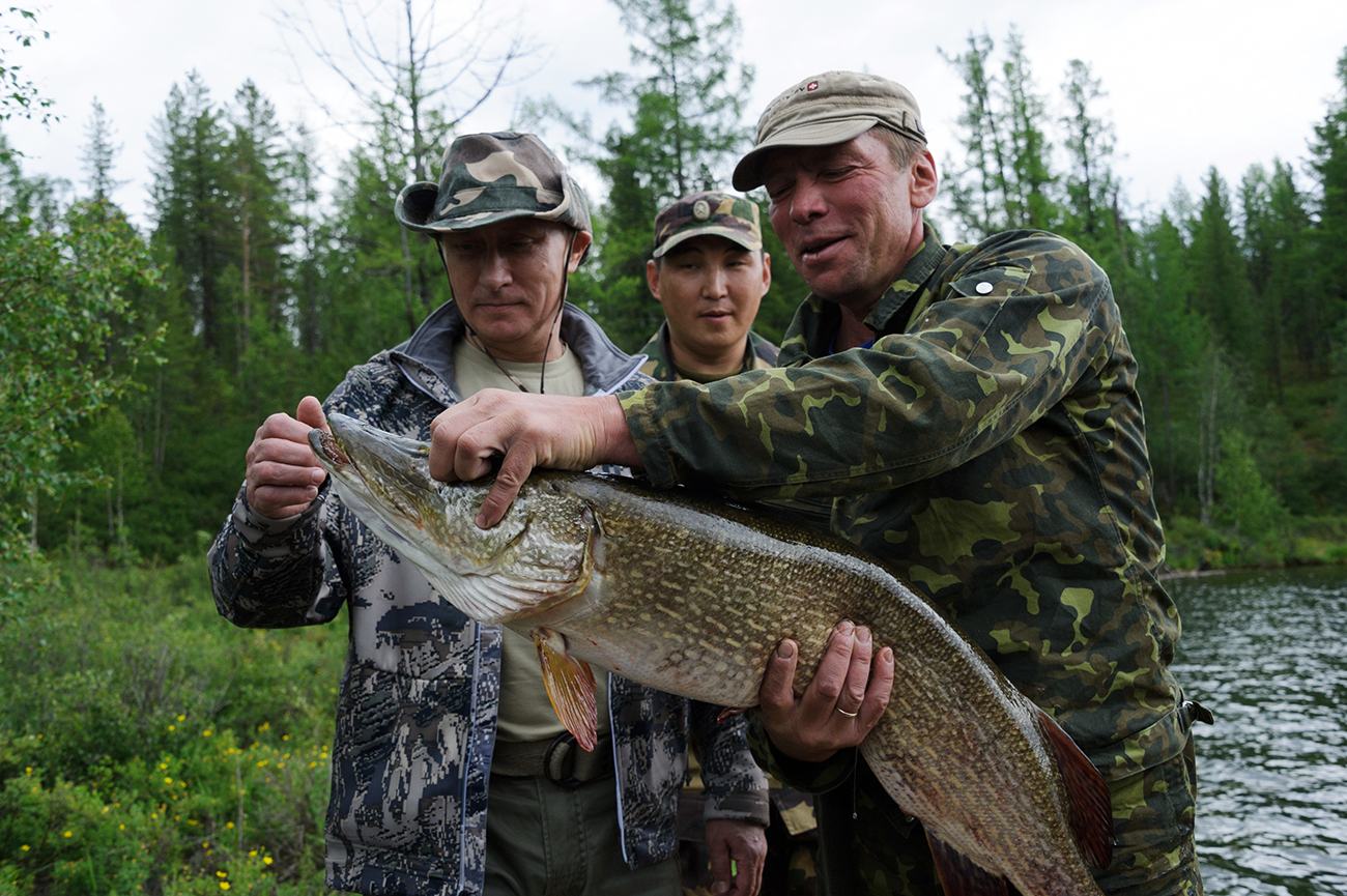 Russian President Vladimir Putin, left, on a fishing trip, 20 July 2013.