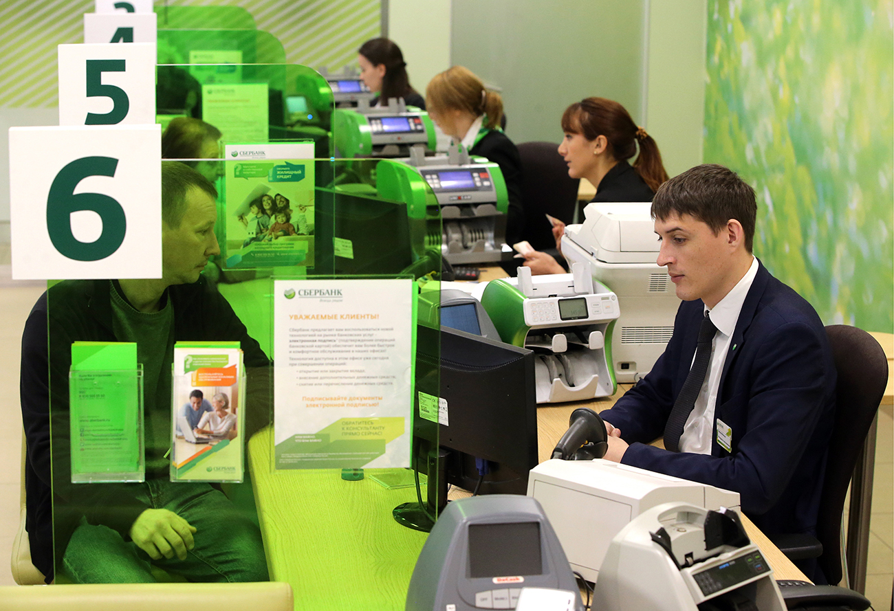 Photo: Staff and custmers in a Sberbank branch in St. Petersburg, Russia.