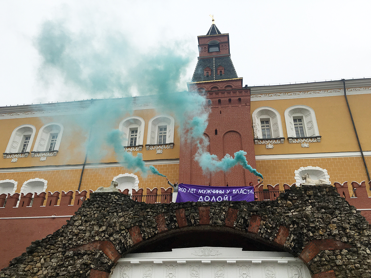 "MOSCOW, RUSSIA - MARCH 8, 2017: Feminist activists unfurl a banner with a message reading ""Men have been in power for 200 years. Down with it!"" and light smoke flares outside the Kremlin on the International Women's Day"