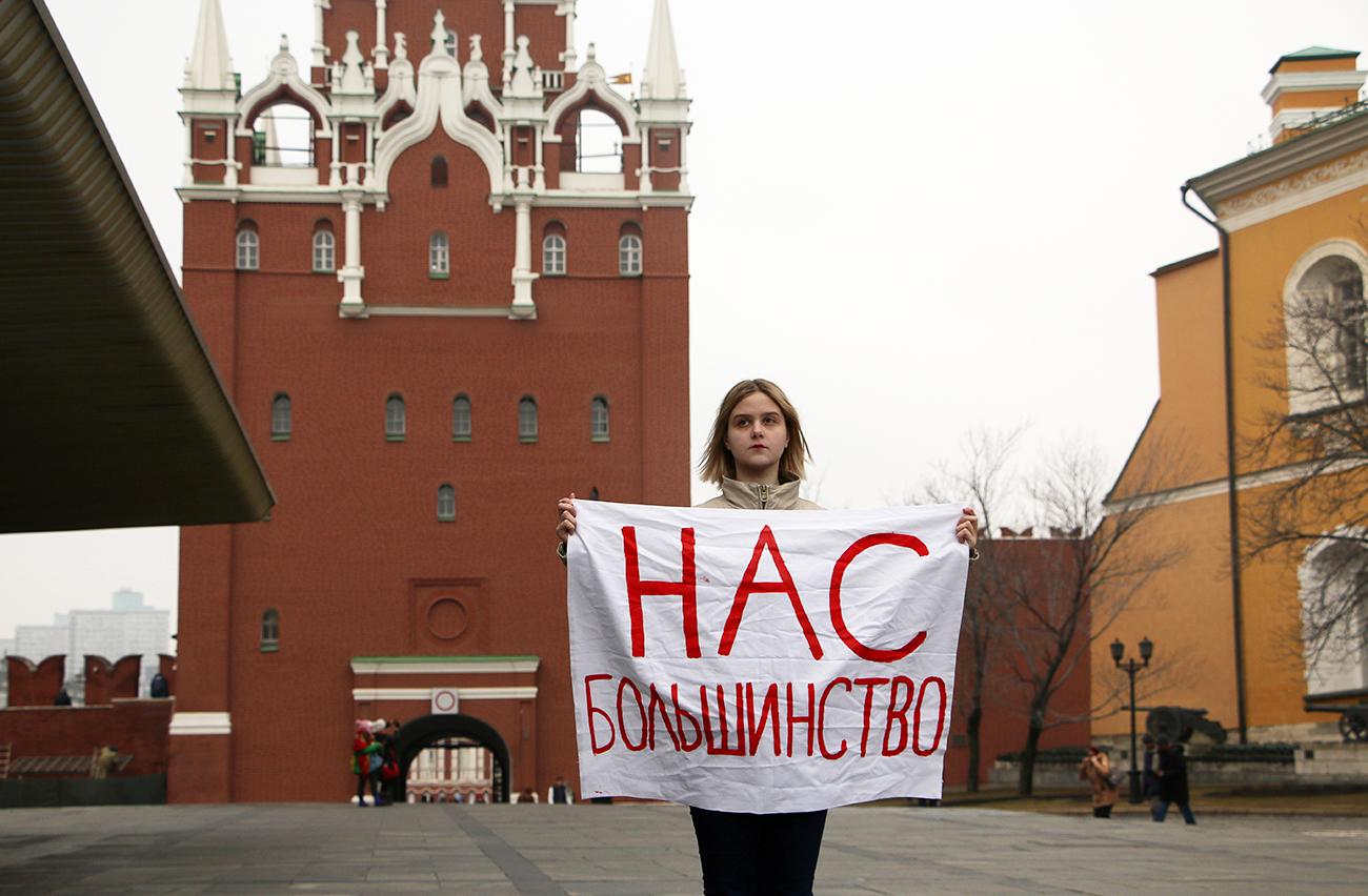 """Feminista con un cartel en el que está escrito """"Somos mayoría"""" frente al Kremlin."""