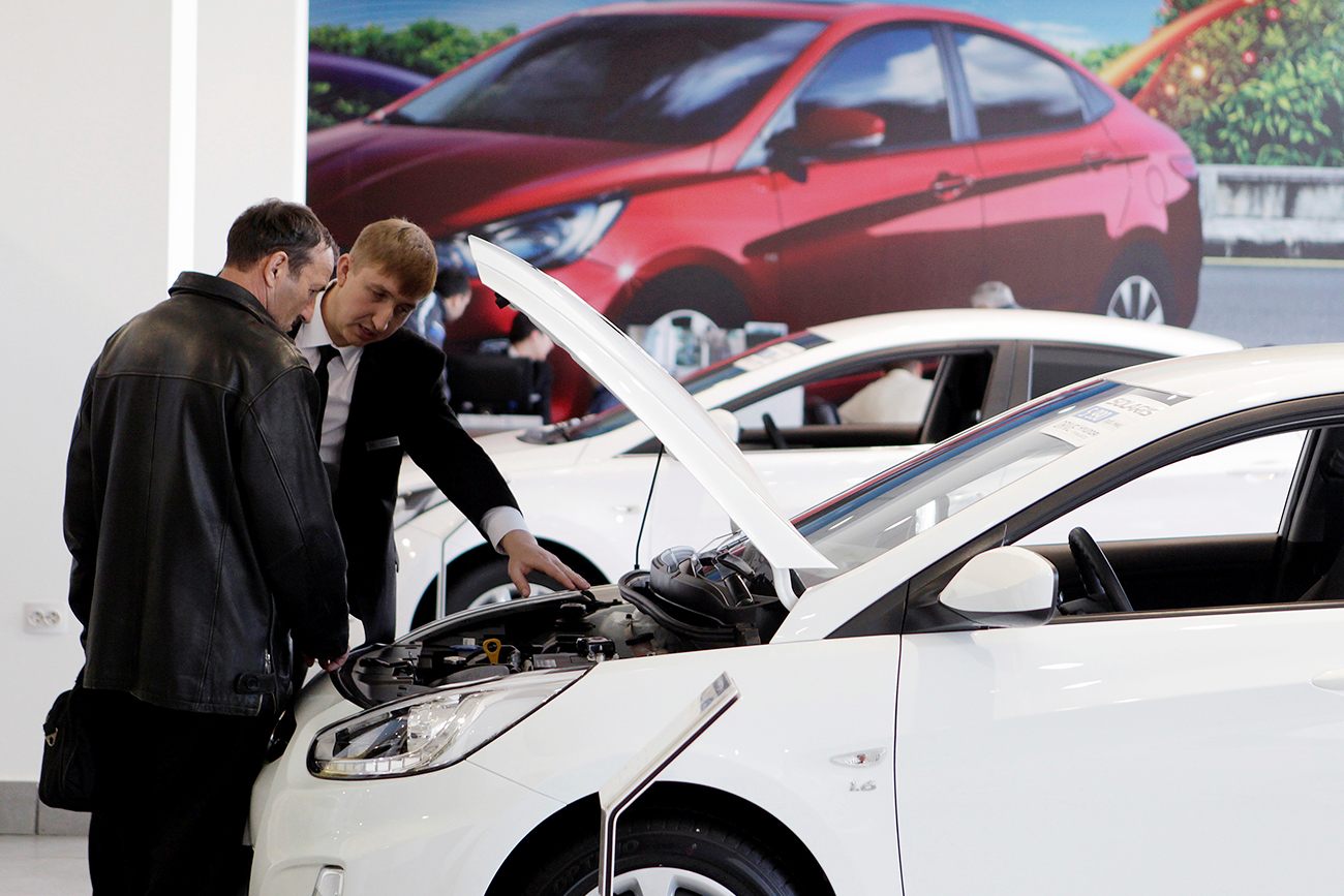 A customer listens to an employee near a Hyundai Solaris car at a showroom of a dealership in Stavropol, southern Russia.