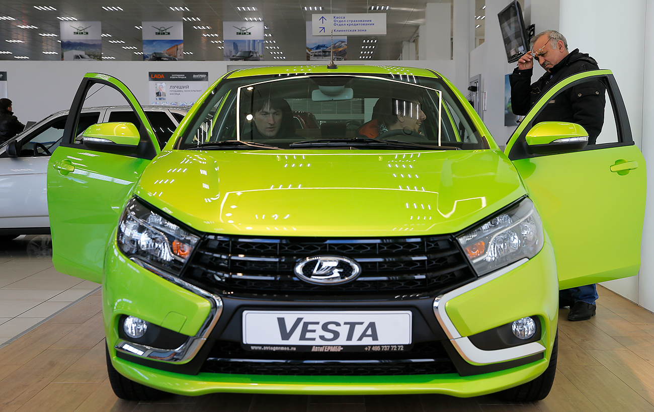 Visitors sit inside a Lada Vesta car, produced by the Russian automobile maker AvtoVAZ, at the 'AvtoGermes' dealership in Moscow, Russia, March 14, 2016.