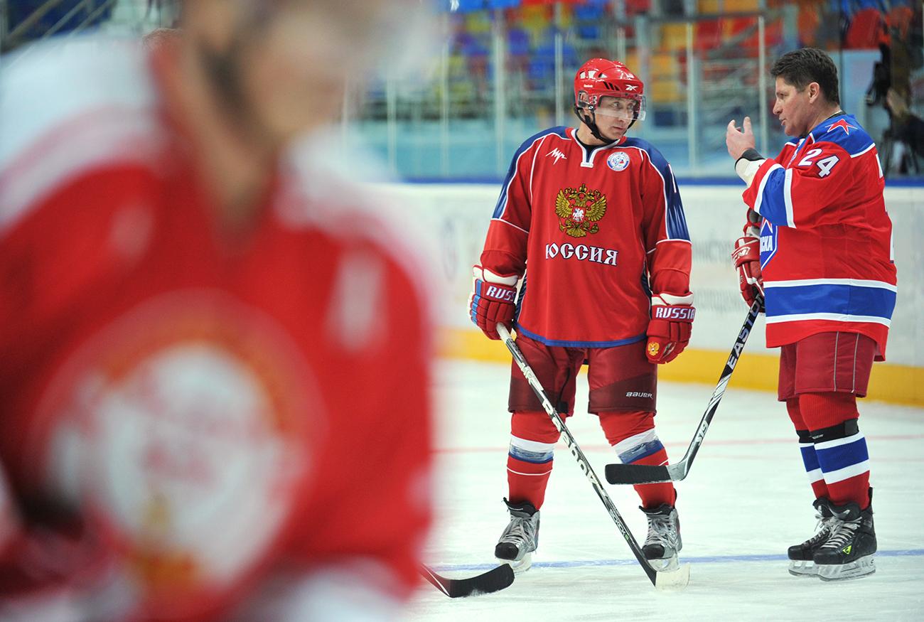 """Takrat še premier Vladimir Putin se pogovarja s hokejsko legendo Sregejem Makarovim med treningom s klubom """"hokejskih legend Sovjetske zveze"""" v areni Megasport v Moskvi, 18. novembra 2011/Reuters"""