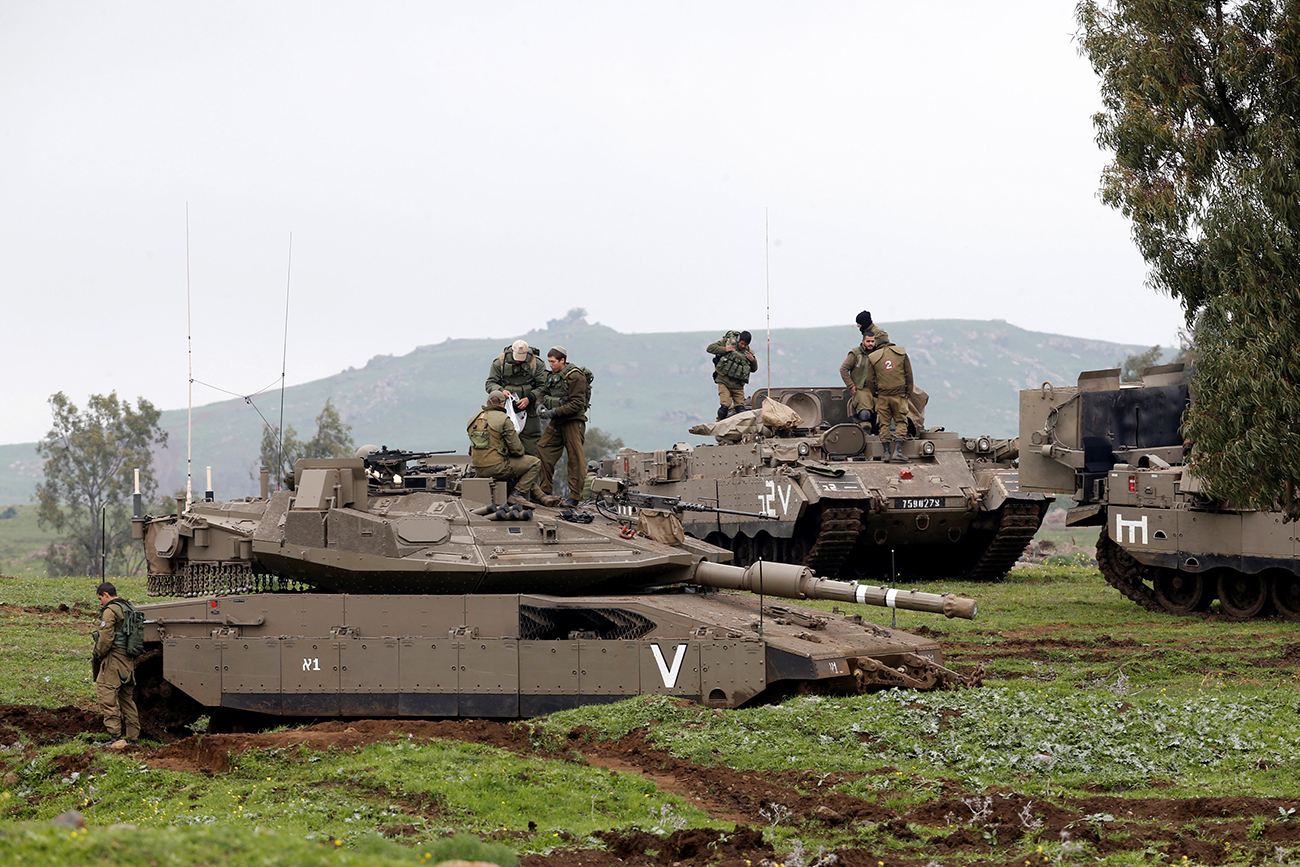 Israeli soldiers stand on top of a tank (front) and an armoured personnel carrier as they take part in an exercise in the Israeli-occupied Golan Heights, near the ceasefire line between Israel and Syria, March 20, 2017.