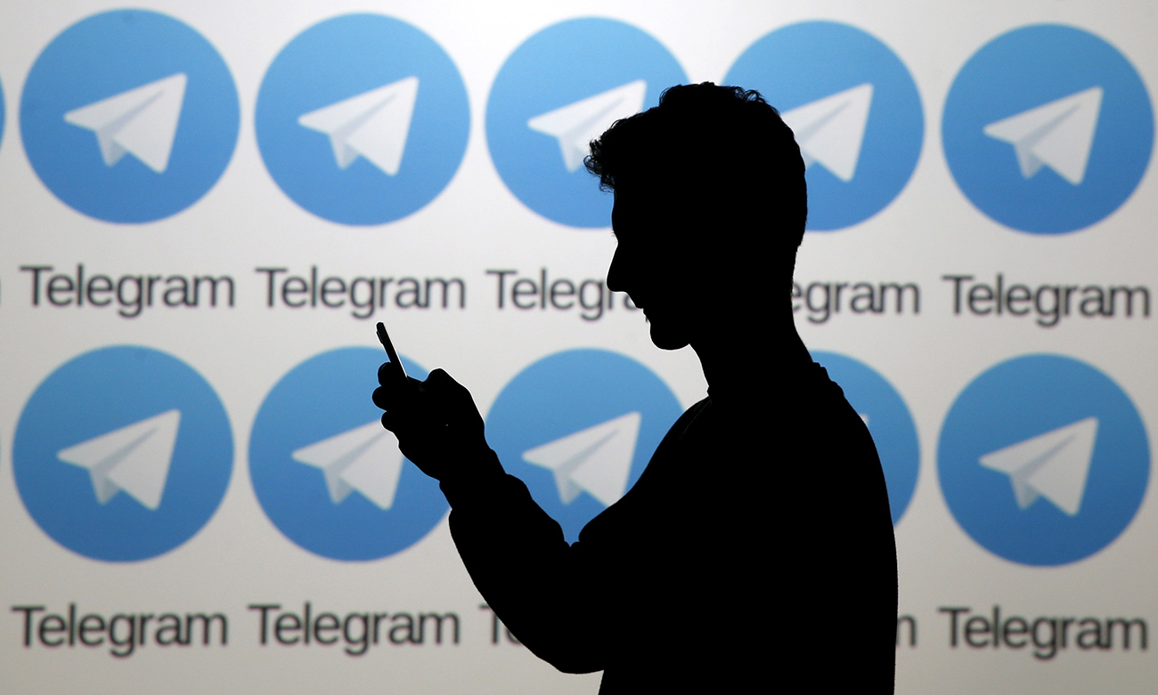 A man poses with a smartphone in front of a screen showing the Telegram logosю
