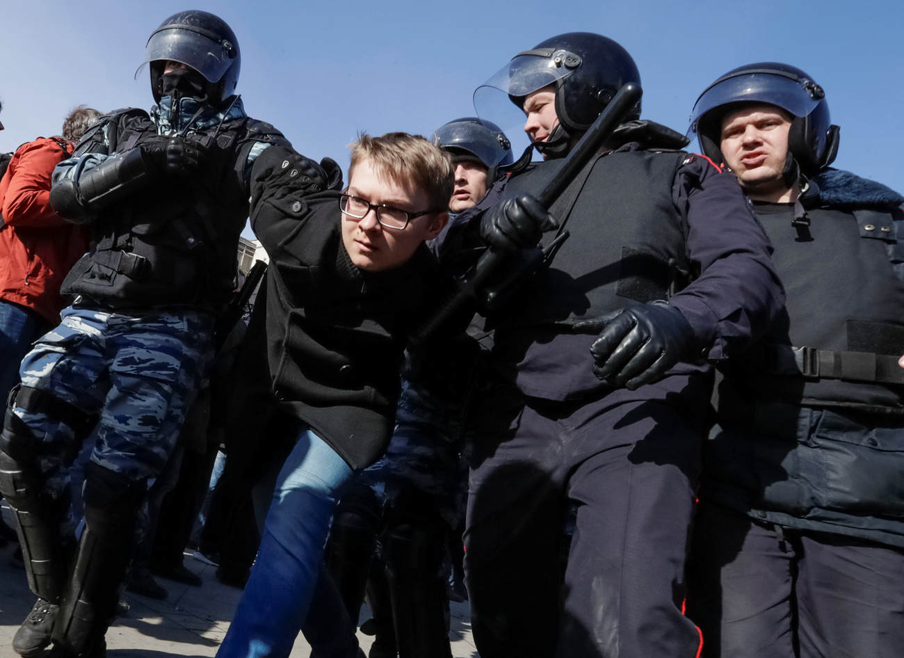 Law enforcement officers detain an opposition supporter during a rally in Moscow, March 26, 2017.