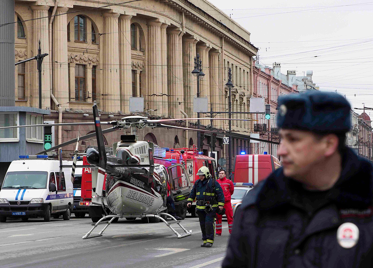 Members of the Emergency services stand next to a helicopter outside Tekhnologicheskiy Institut metro station in St. Petersburg, April 3, 2017