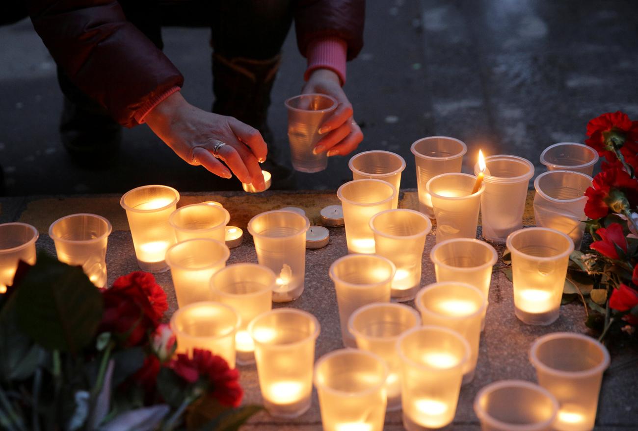 A woman leaves a candle during a memorial service for victims of a blast in St.Petersburg metro, outside Spasskaya metro station in St. Petersburg, April 3, 2017.