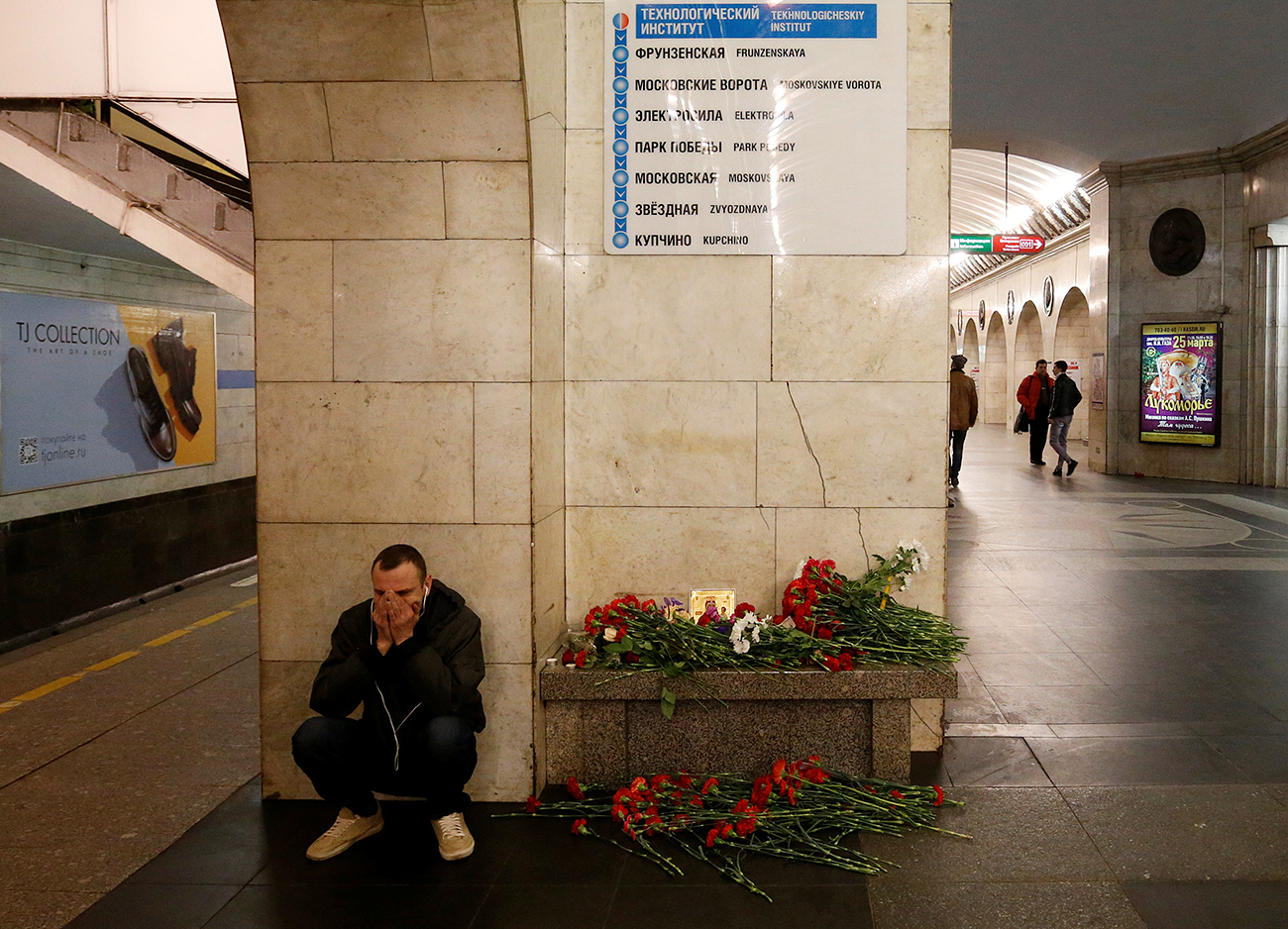 A man reacts next to a memorial site for the victims of a blast in St. Petersburg metro, at Tekhnologicheskiy institut metro station in St. Petersburg, April 4, 2017.
