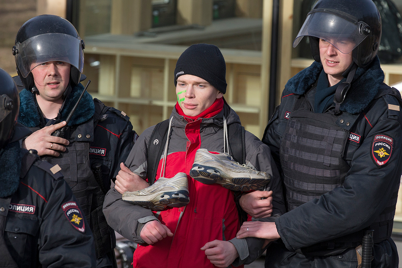A protester with trainers on his neck, which has become a symbol of corruption, is detained in Moscow on March 26, 2017.