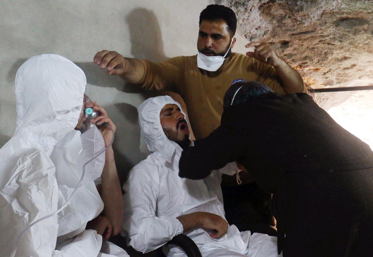 Seorang pria bernapas melalui masker oksigen sementara yang lainnya menerima perawatan, setelah apa yang digambarkan para petugas penyelamat sebagai serangan gas di kota Khan Sheikhoun di Provinsi Idlib yang dikuasai pemberontak, Suriah, 4 April 2017.