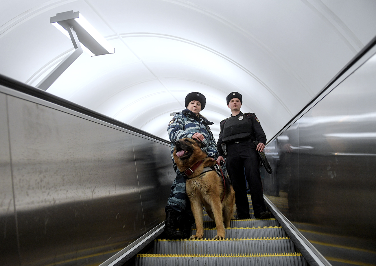 Moscow metro dog service center's employees patrol a Moscow metro station with a dog.