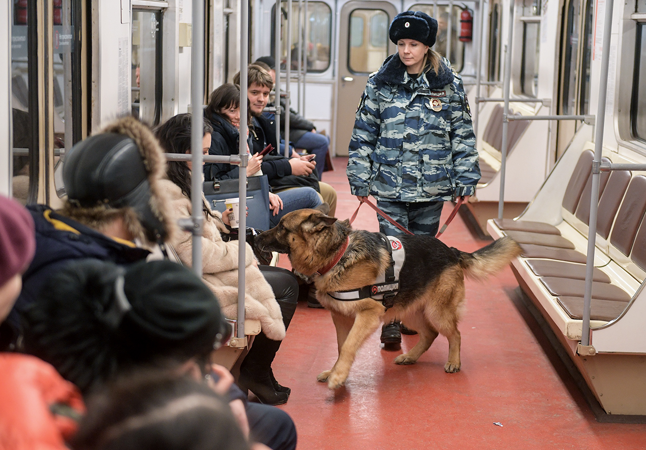 Moscow metro dog service center's employee patrols a Moscow metro station with a dog.