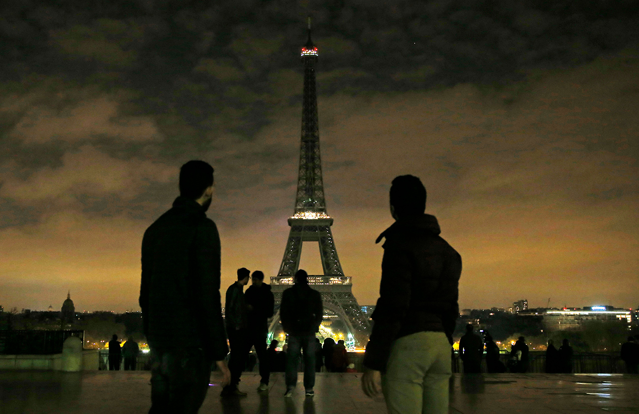 People gather at Trocadero plaza as the lights of the Eiffel tower falls dark at midnight in Paris, France, Wednesday, April 5, 2017. Paris mayor Anne Hidalgo says the Eiffel Tower will fall dark overnight to honor the victims of the St. Petersburg subway bombing.
