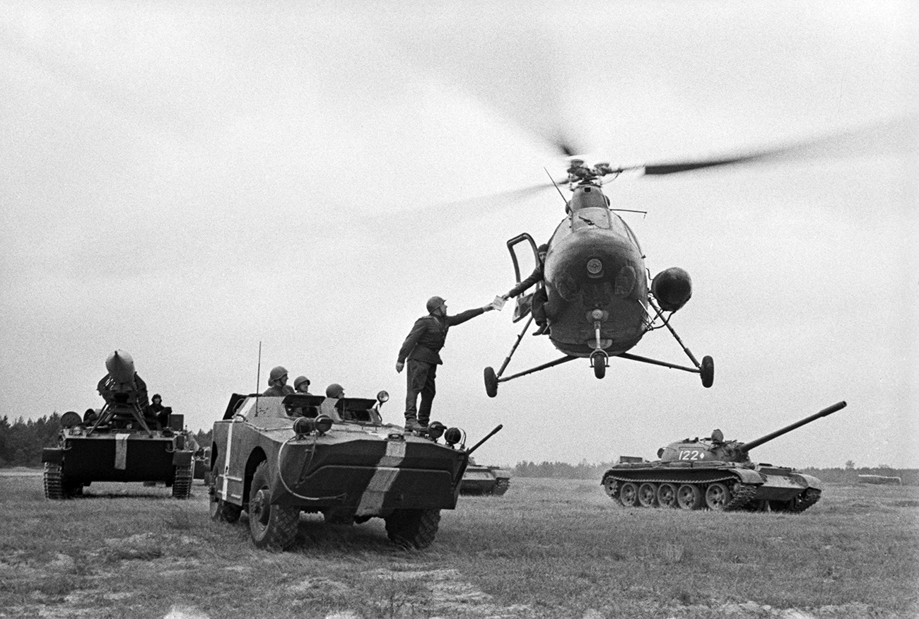 A crew of the Mi-2 helicopter transmits a map of the further route to the commander of the BRDM accompanying the 2P16 launcher with the 3R9 missile of the Luna 2К6 missile system during military exercises, USSR. September 1966. / Yevgeny Kassin, Mark Redkin/TASS