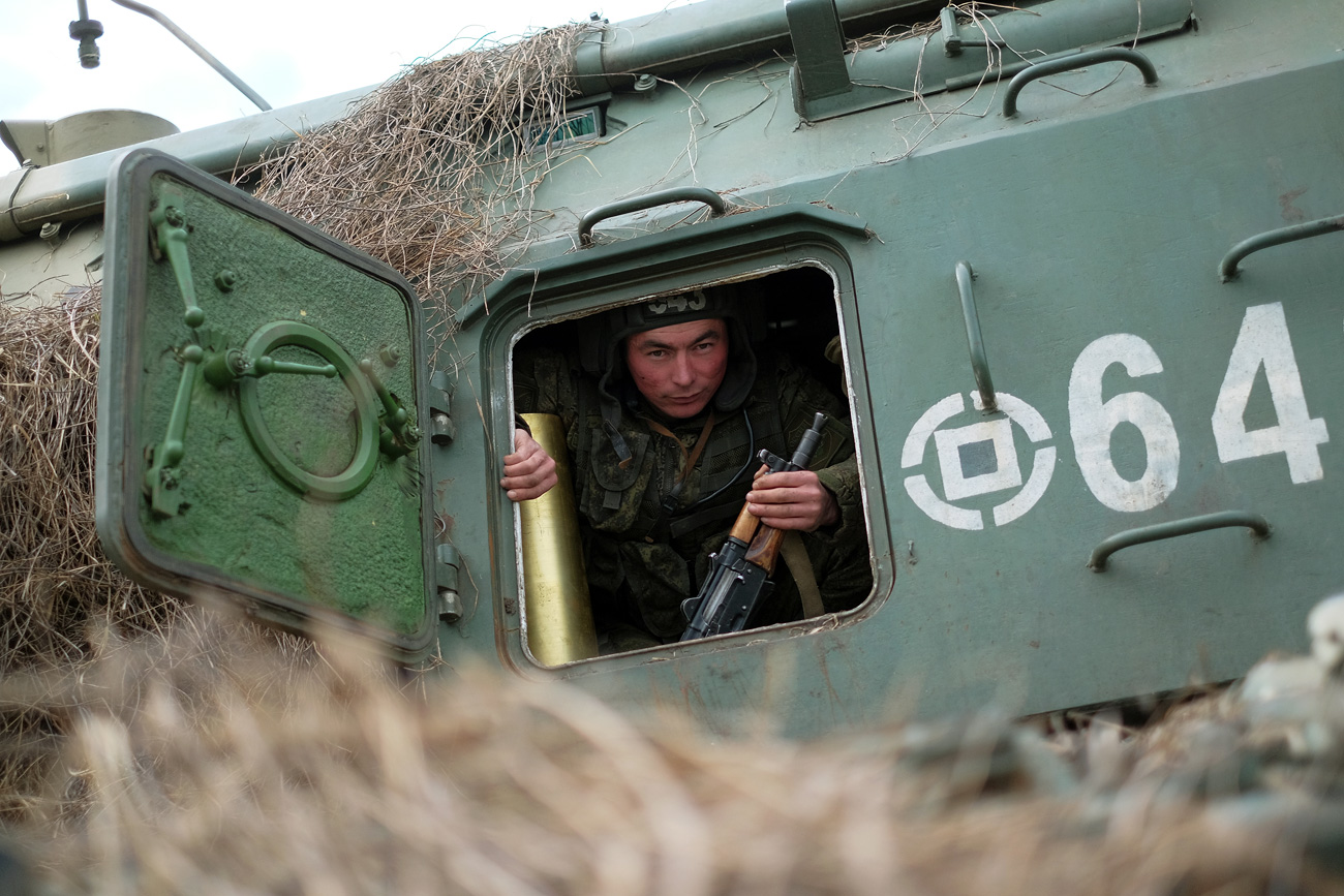 A soldier in the cabin of a Msta-S self-propelled artillery system at Molkino base