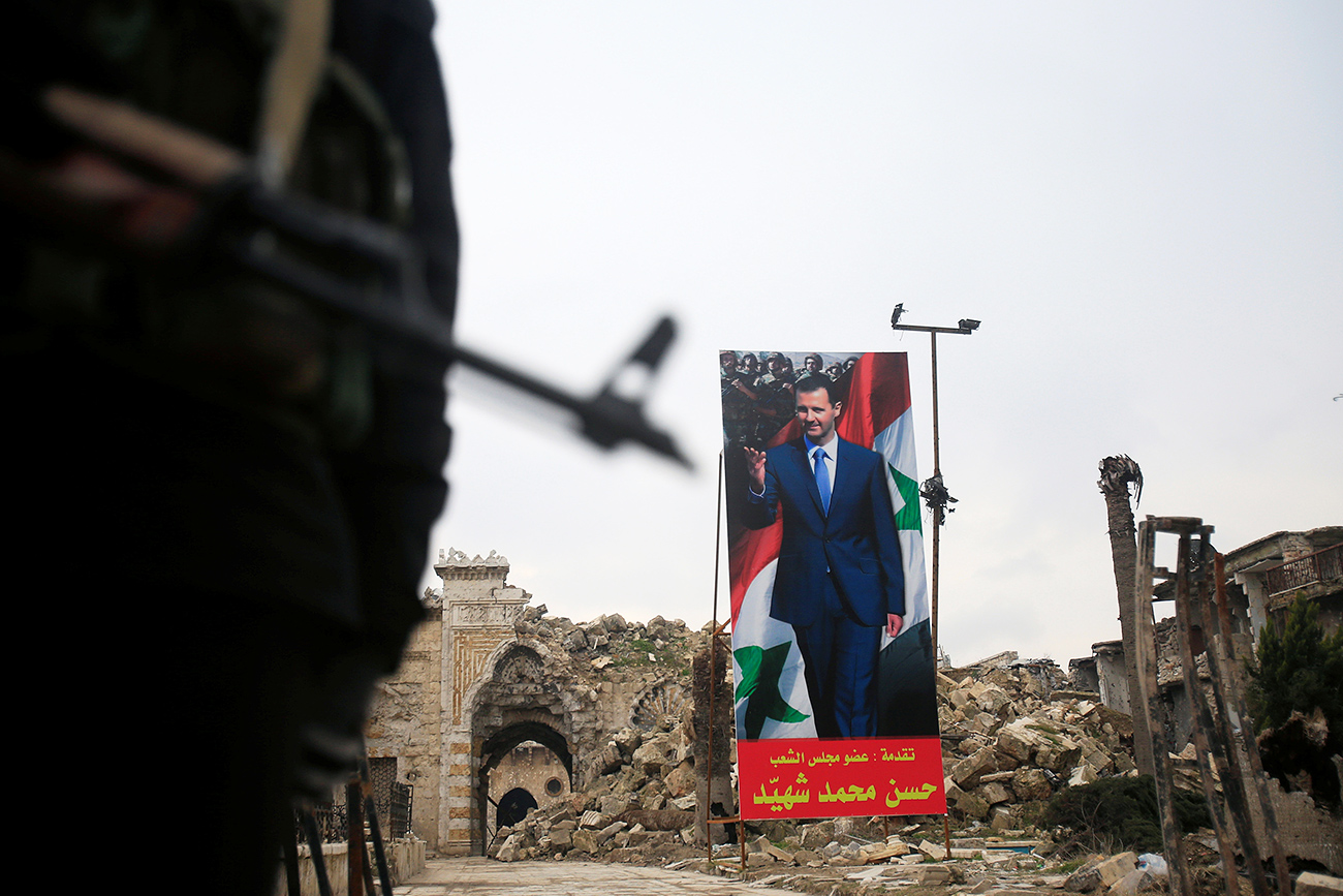 A Syrian army soldier stands guard as a poster depicting Syria's President Bashar al-Assad is seen in the background in the Old City of Aleppo, Syria, Jan. 31, 2017