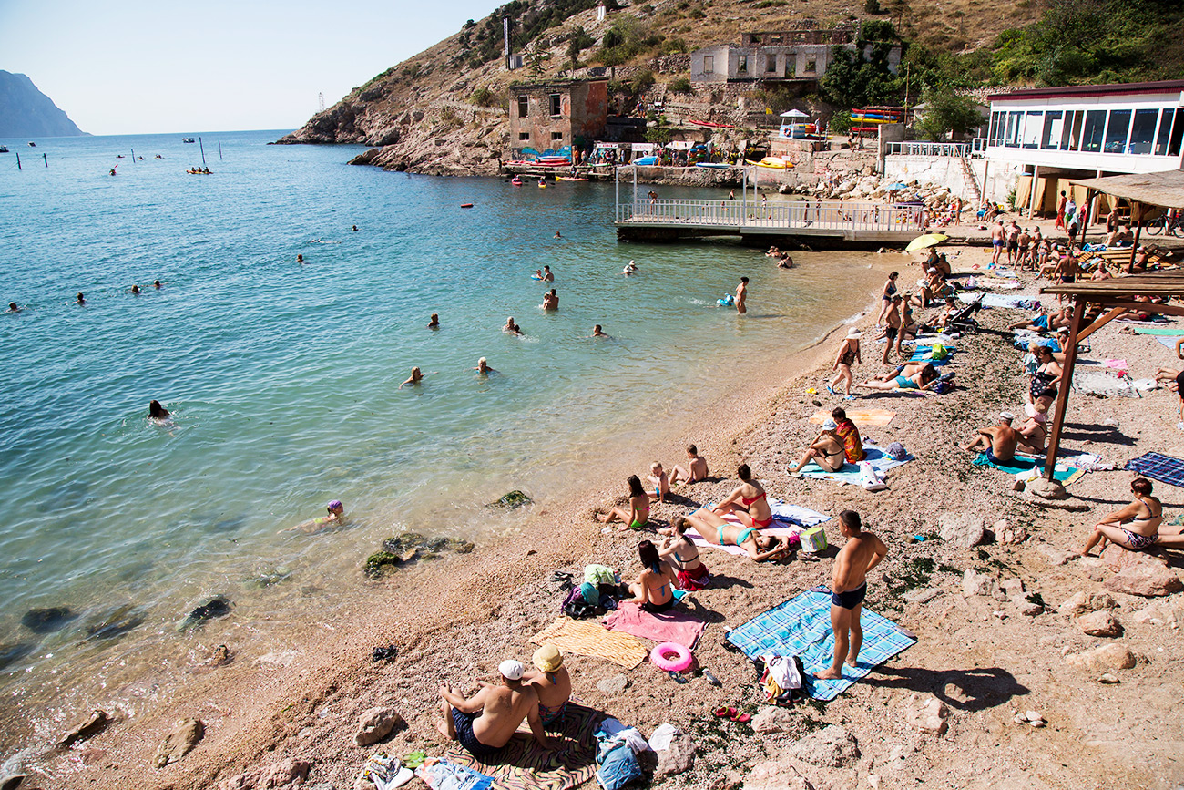 People gather at the beach area of the Black Sea, in Balaklava's bay, a part of Sevastopol on the Crimean Peninsula.