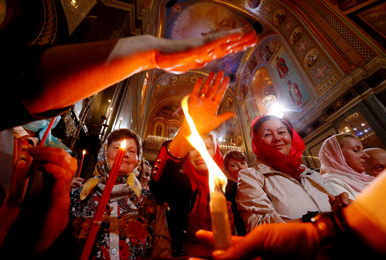 Worshippers reach out to touch candles with Holy Fire during an Orthodox Easter service at the Christ the Saviour Cathedral in Moscow, Russia