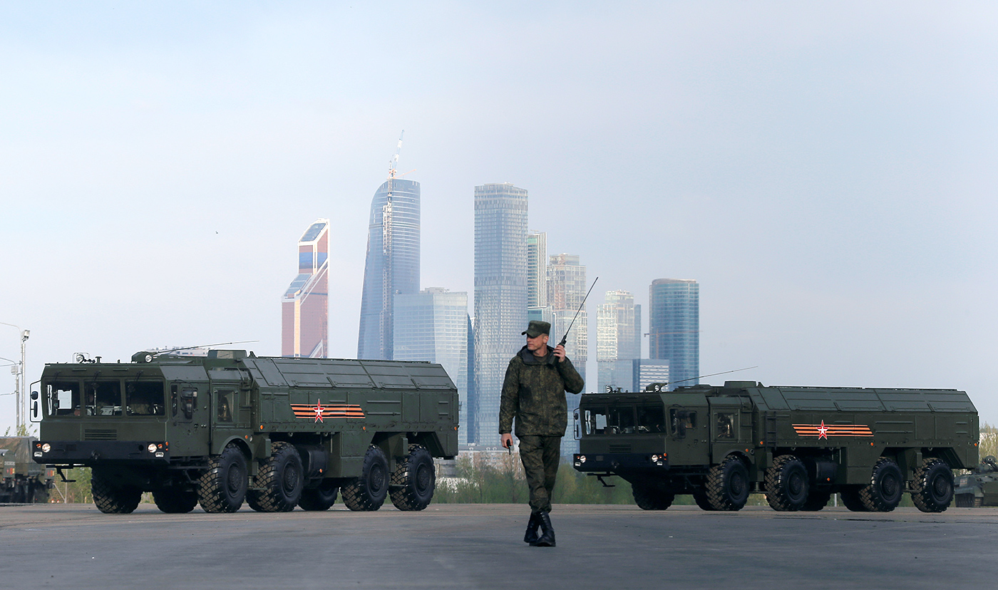 "A Russian serviceman walks past Russian Iskander-M missile launchers before a rehearsal for the Victory Day parade, with the Moscow International Business Center also known as ""Moskva-City"" seen in the background, at a range in Moscow, Russia, May 5, 2016"